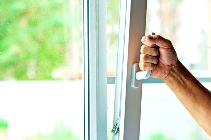 a hand pulling open a window