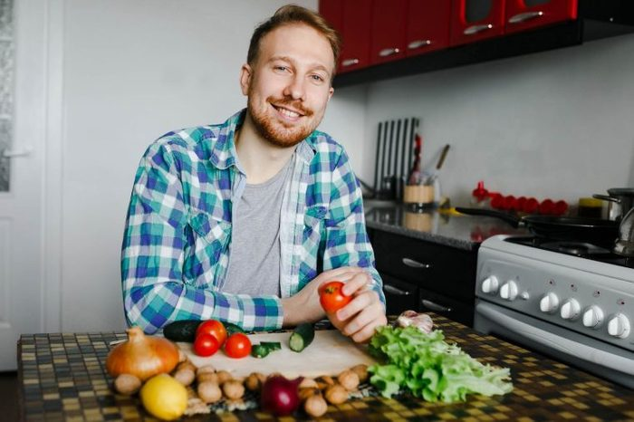 man in kitchen with fresh vegetables on and around a chopping board