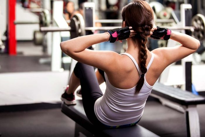 young woman doing sit ups at gym