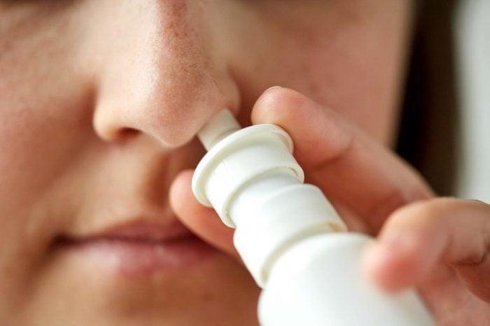 close up of a woman using a nasal inhaler