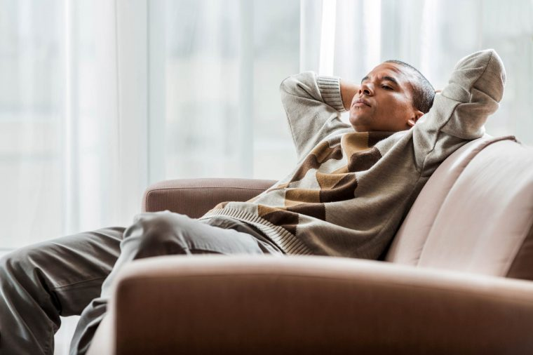 man relaxing on couch with eyes closed, hands behind head