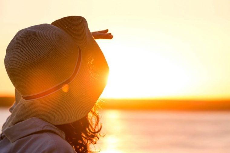 woman wearing a hat gazing at a sunset