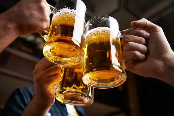 hands clinking together three mugs of beer in a toast