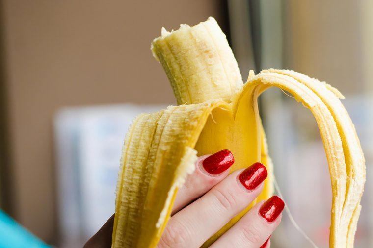 woman's hand holding a half-eaten banana
