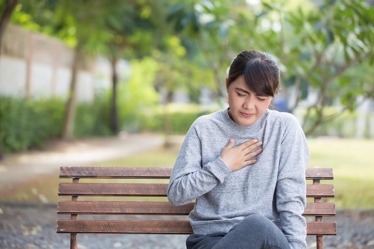 Asian woman sitting on a bench outdoors holding her hand to her chest