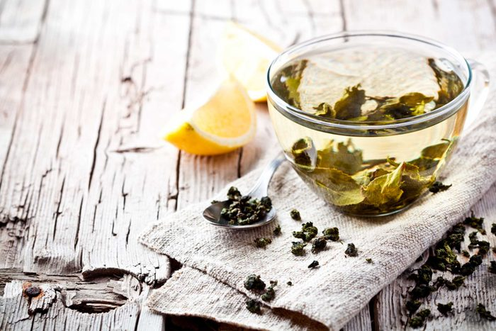 Cup of green tea with lemon on side