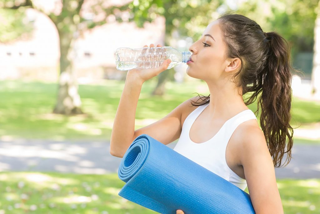woman with rolled yoga mat drinking water