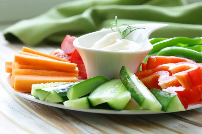 sliced vegetables on a plate surrounding cup of dip