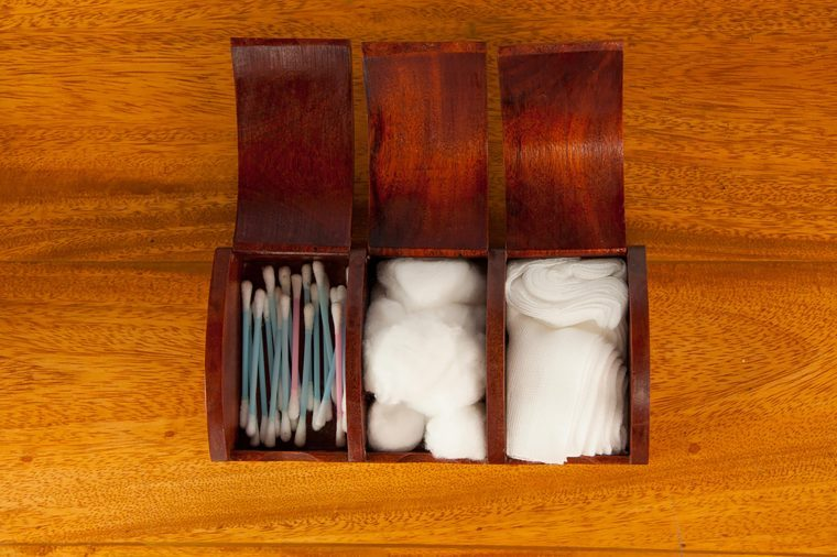 wooden box with cotton swabs, balls, and gauze