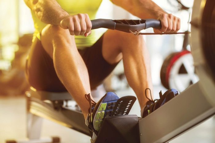 person on rowing machine at gym