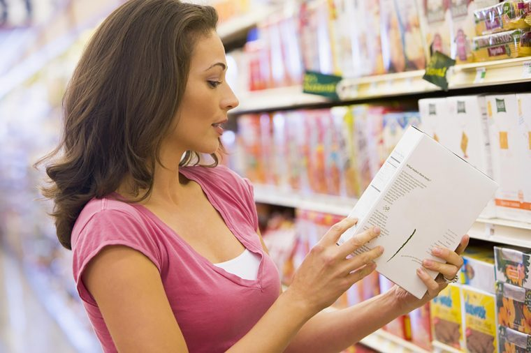 woman reading labels at grocery store