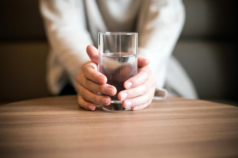 a person holding a glass of water