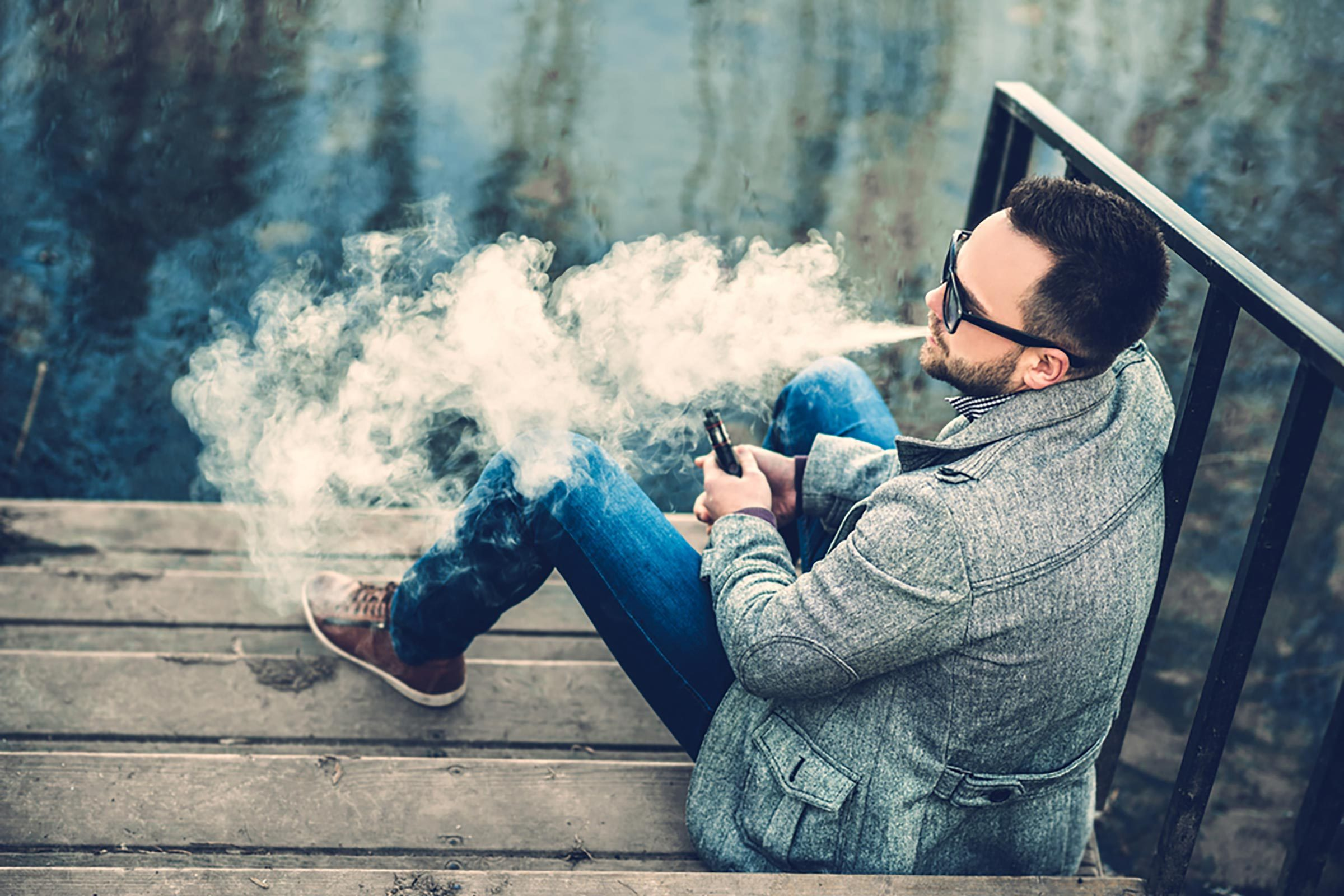 man vaping outdoors on steps