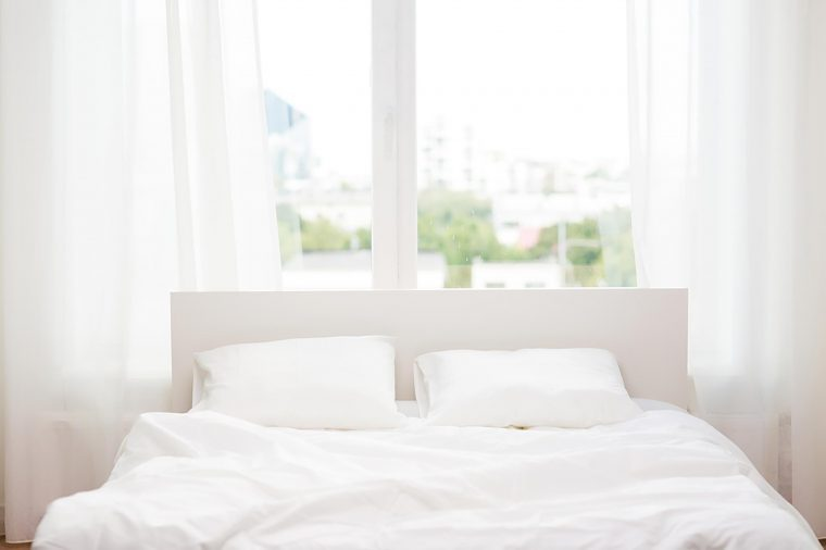 white bed in front of window