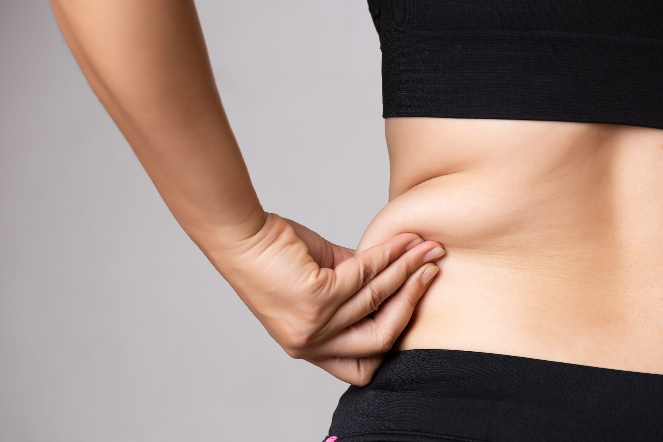 woman grabbing excess fat on side of her stomach and back