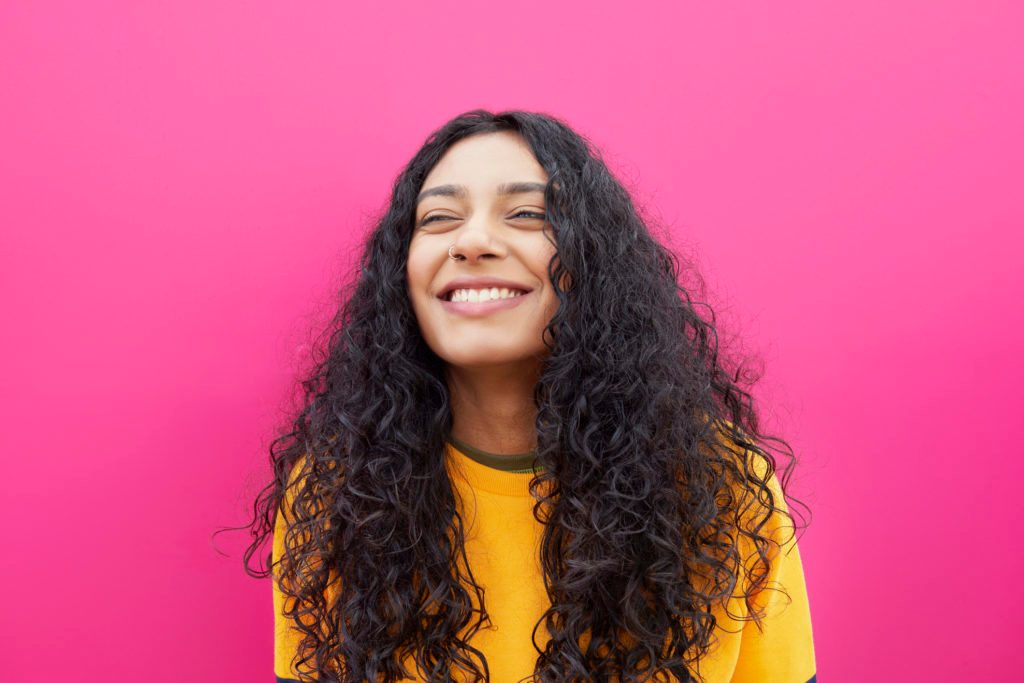 young woman smiling on pink background