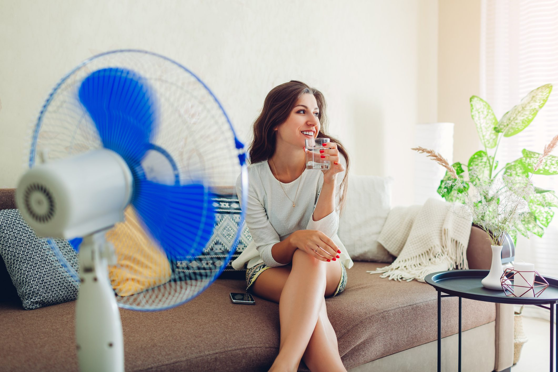 woman sitting on couch in front of fan and drinking a glass of water