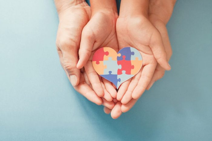 adult and child hands holding autism puzzle heart