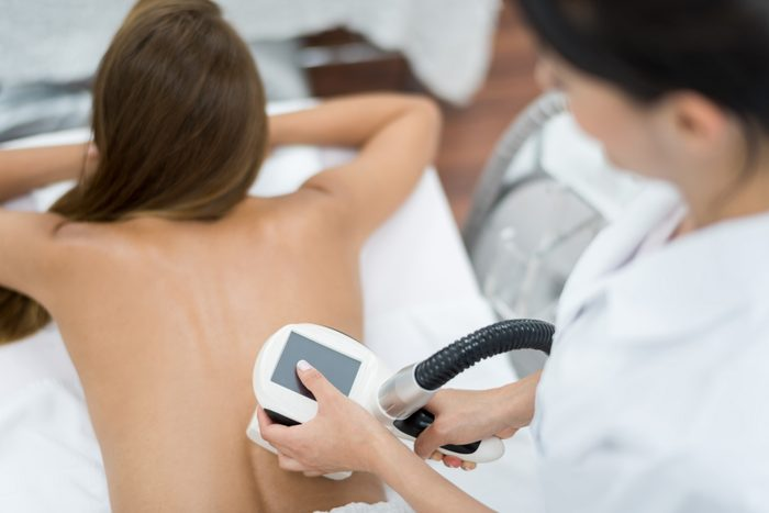 woman getting laser therapy on back