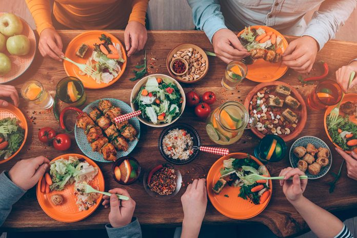 people eating delicious food at table