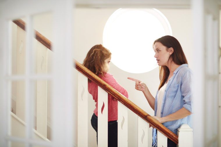 mother disciplining young daughter at home