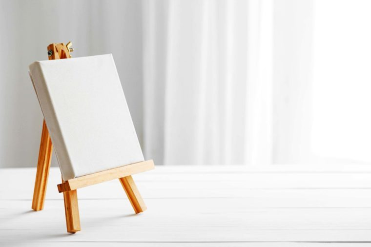 Blank easel in a white room.