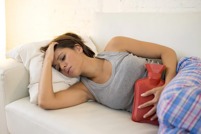 woman with cramps holding hot water bottle to torso