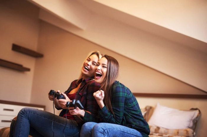 Two women playing video games and laughing.