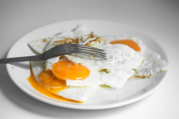 eggs over easy on a white plate with a fork