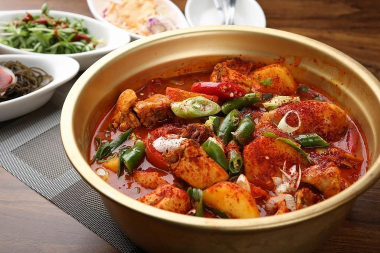 Spicy food with green onions in a bowl on a table.