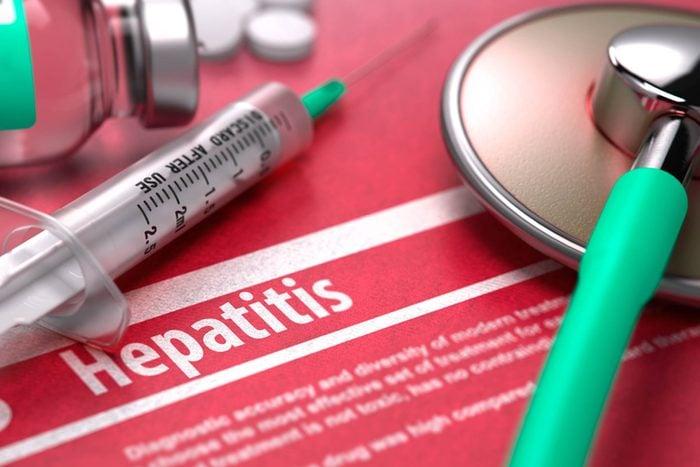 syringe and stethoscope over hepatitis info