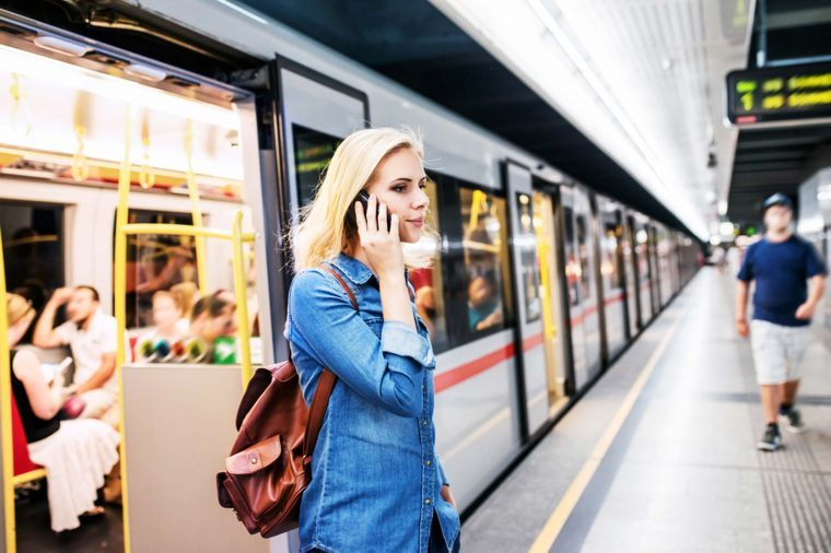 woman talks on phone as she departs commuter train