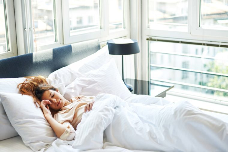 A woman lying on a bed sleeping in her high-rise apartment.