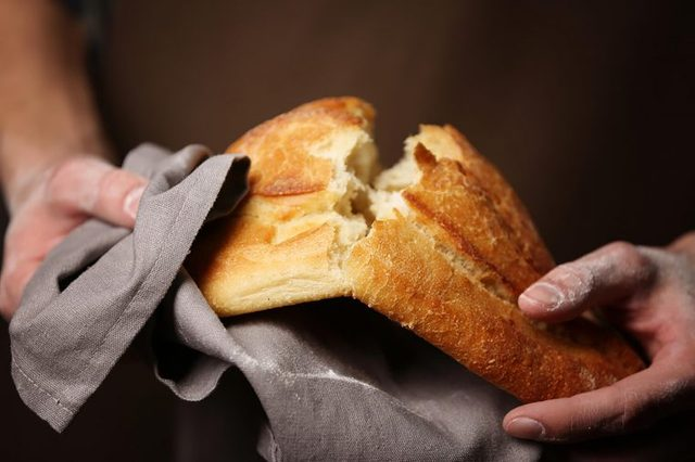 person breaking a loaf of crusty bread in half