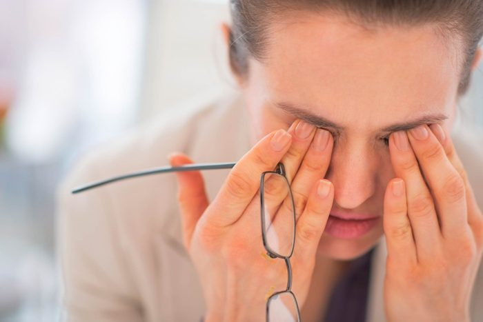 woman leaning forward and rubbing her eyes