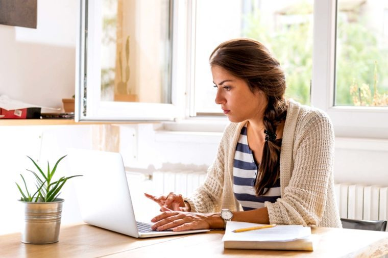 A woman with brown hair working on a laptop.