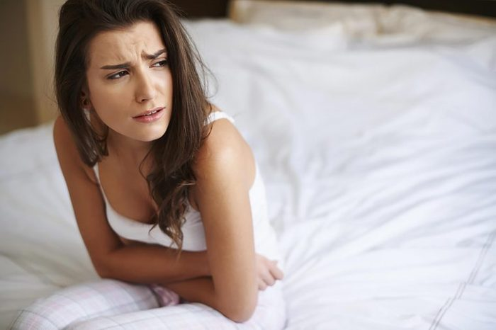 distressed woman hunched over in bed and holding her stomach