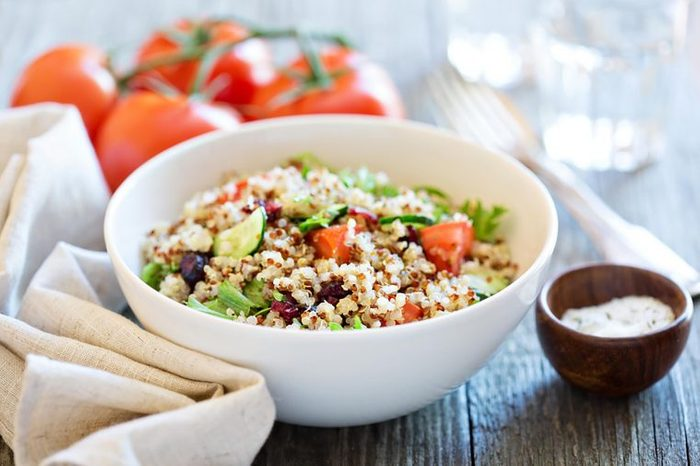 Bowl of quinoa topped with tomato and avocado.