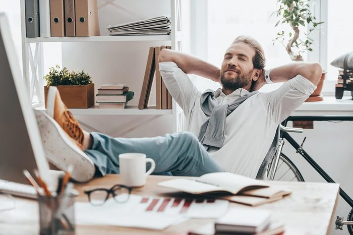 man leaning back in office chair