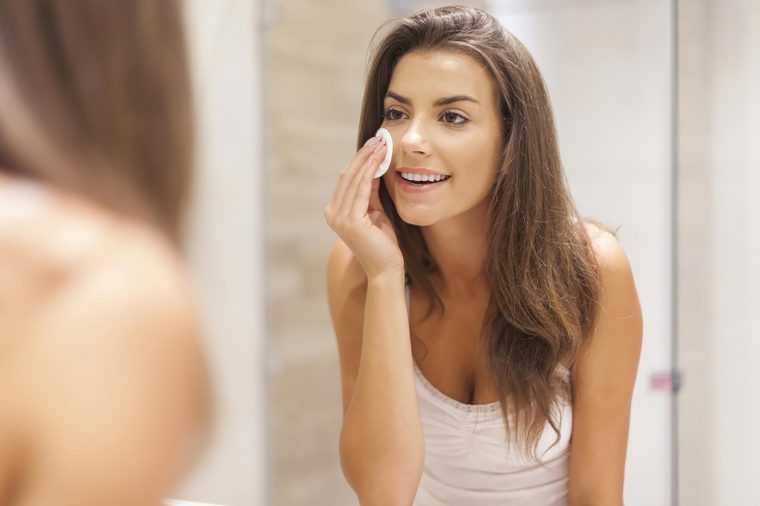 A woman applying a cleansing pad to her skin while standing in front of the mirror.