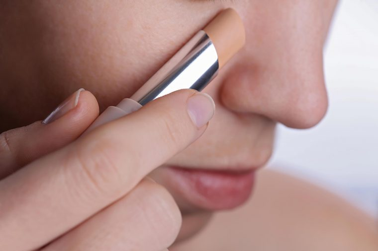 Woman applying a stick of concealer to her cheek.