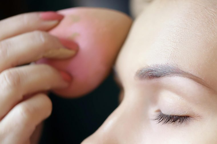 A woman applying foundation to her forehead with a pink beauty blender.