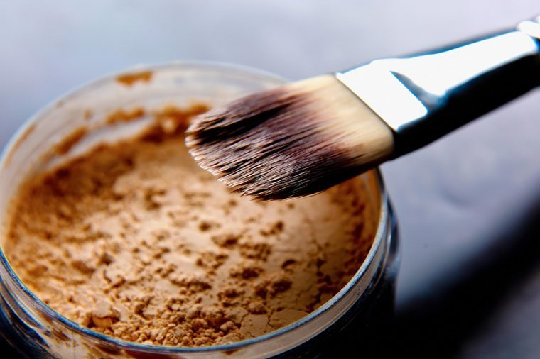 A foundation brush in a jar of makeup powder.
