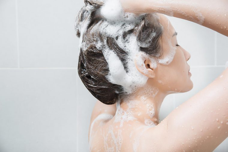 A woman shampooing her hair in the shower.
