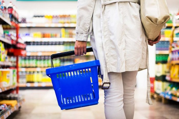 woman carrying basket in grocery store