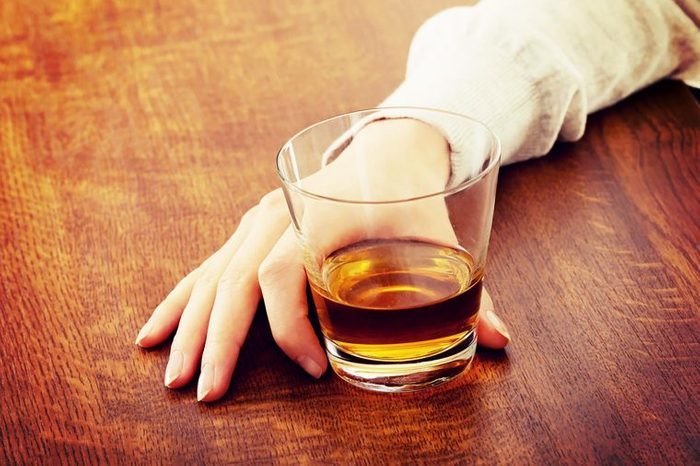 woman's hand holding glass of alcohol