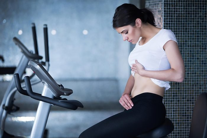 woman looking at her own abs while sitting in gym