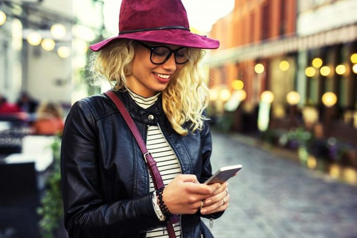 woman in hat texting on phone