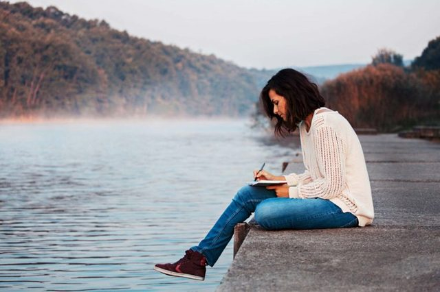 woman sitting on dock writing in journal