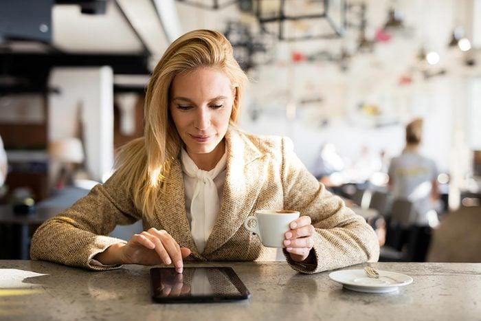 woman in coffee shop on ipad